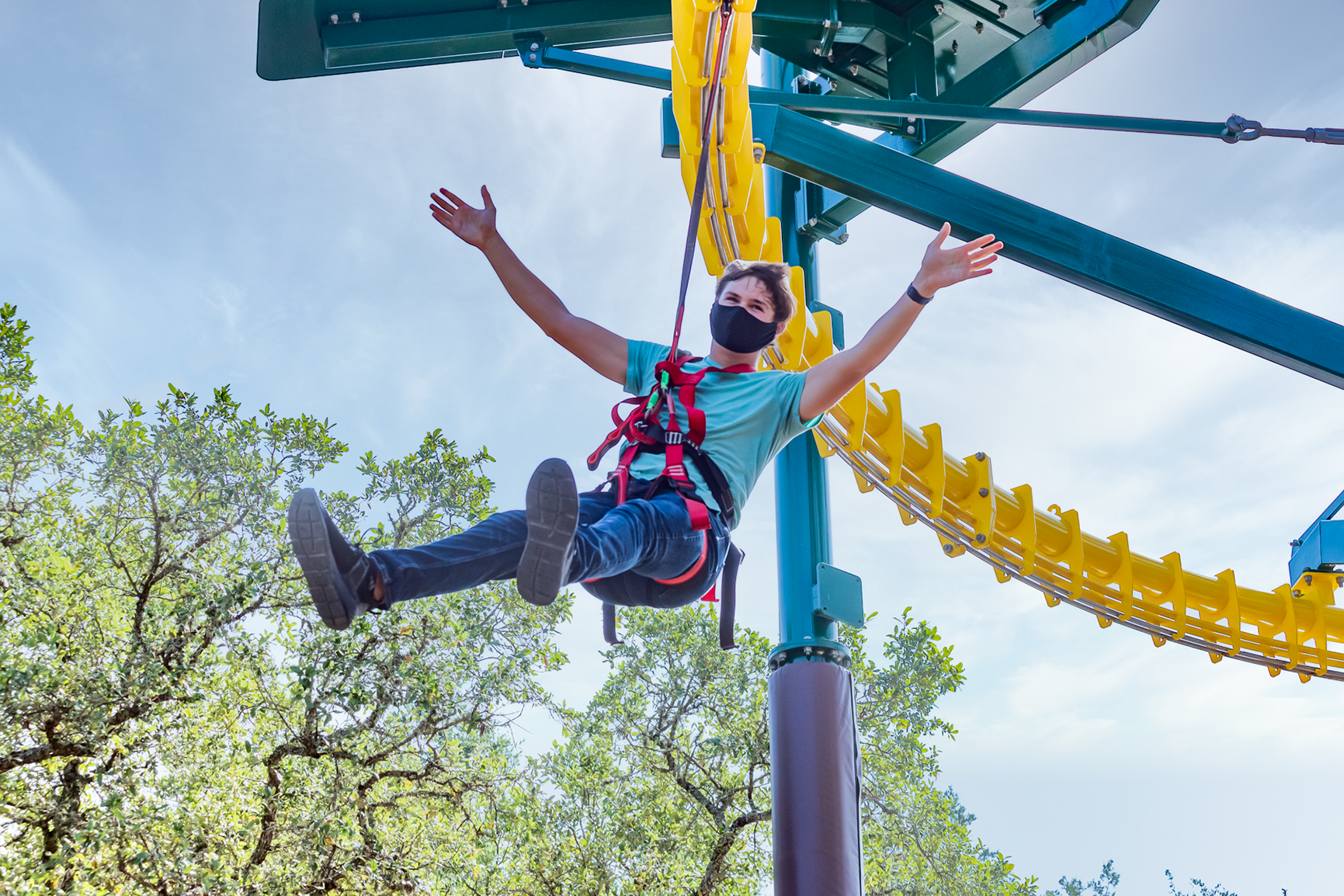 Young man zipping through the air on a zip rail hands free | Natural Bridge Caverns