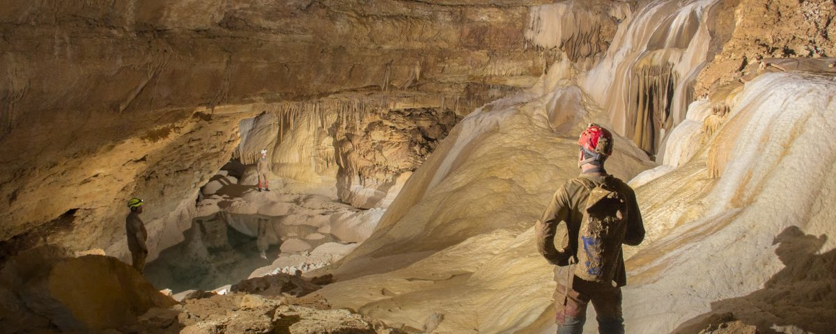 Cavers standing in a newly discovered underground room with water